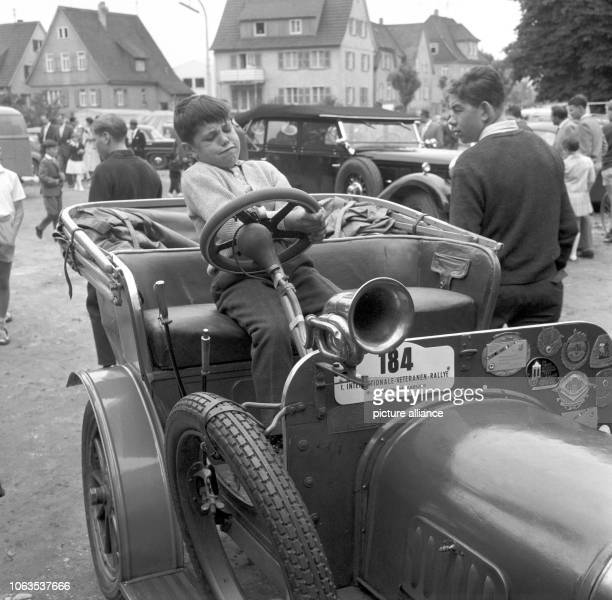 A boy practices at the steering wheel of an oldtimer during the V international veteran rally in Neckarsulm on 21 June 1963   usage worldwide