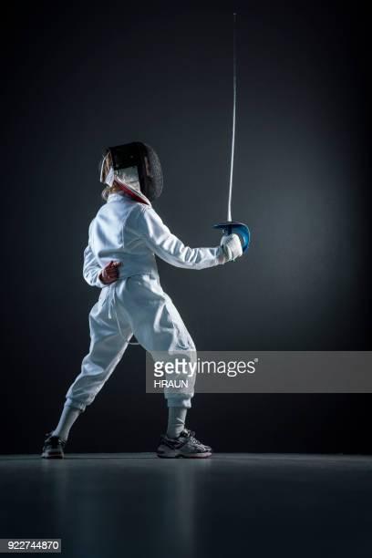 Boy practicing fencing sport over black background