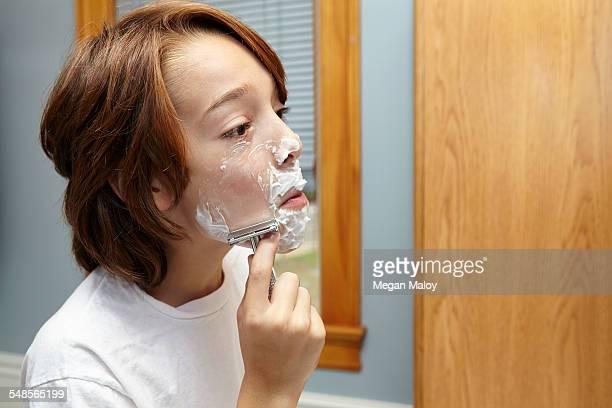 boy practicing shaving with razor in bathroom - indipendenza foto e immagini stock