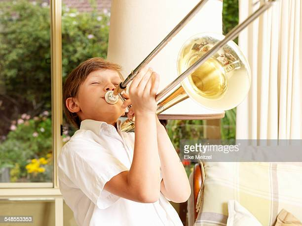 Boy practicing trombone in sitting room