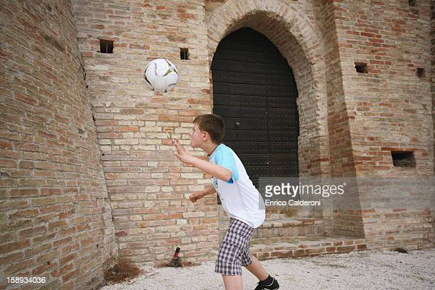 Boy Practicing With Football In Street