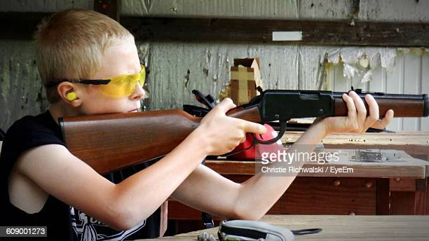 boy practicing with rifle at shooting range - ライフル ストックフォトと画像