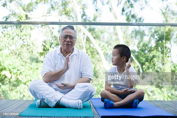 Boy practicing yoga with his grandfather