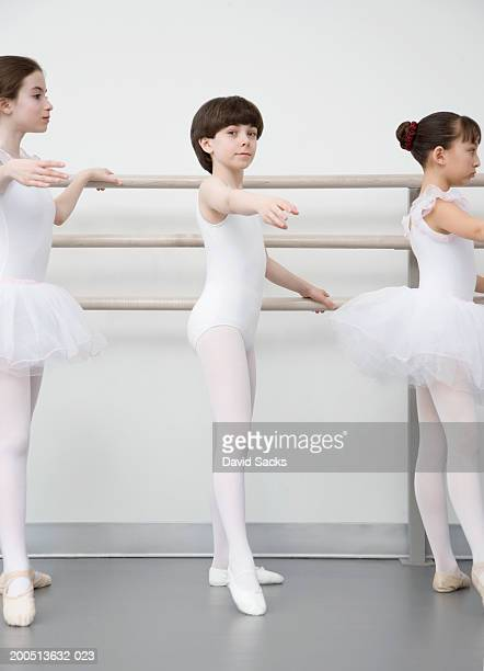 Boy (12-14) practising at bar in ballet class, portrait