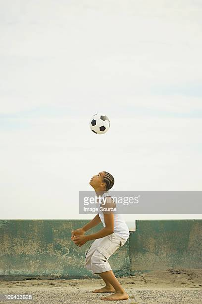 Boy practising heading football by wall