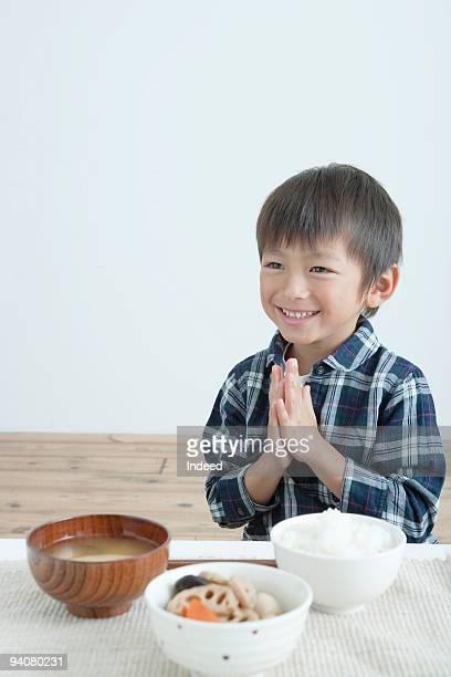 boy praying at table - 男の子一人 ストックフォトと画像