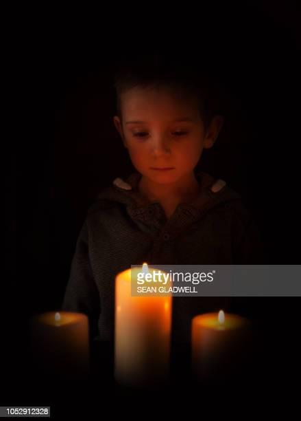 boy praying by candle - osterfeuer stock-fotos und bilder