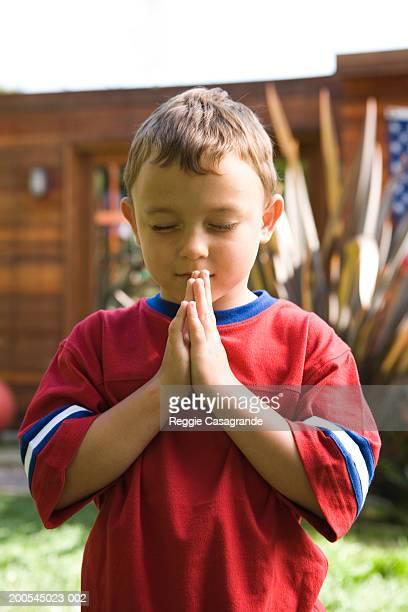 Boy (4-6) praying in yard
