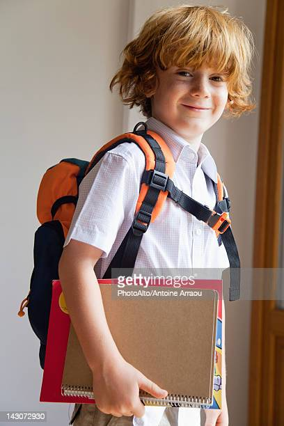 Boy prepared for school, carrying backpack and notebooks
