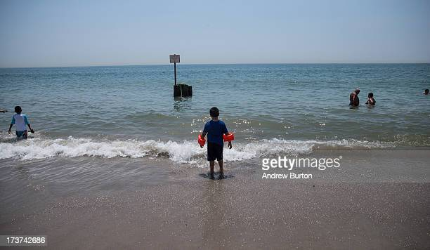 Boy prepares to go swimming at Rockaway Beach during a heat wave on July 17, 2013 in the Rockaway Beach neighborhood of the Queens borough of New...