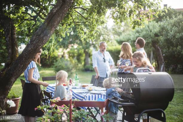 boy preparing food on barbecue grill with mother while family enjoying at dining table in backyard party - medium group of people stock pictures, royalty-free photos & images