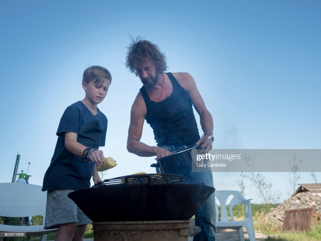 Boy preparing food with his father : Stock Photo