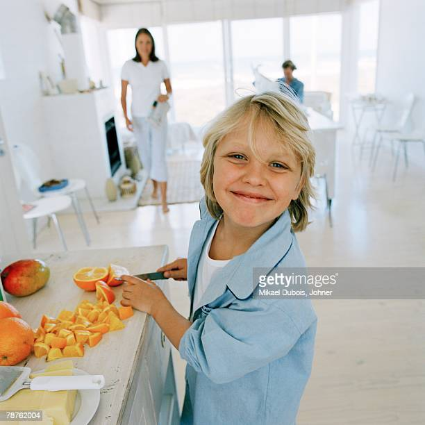 boy preparing fruit for breakfast in the kitchen. - famiglia con figlio unico foto e immagini stock