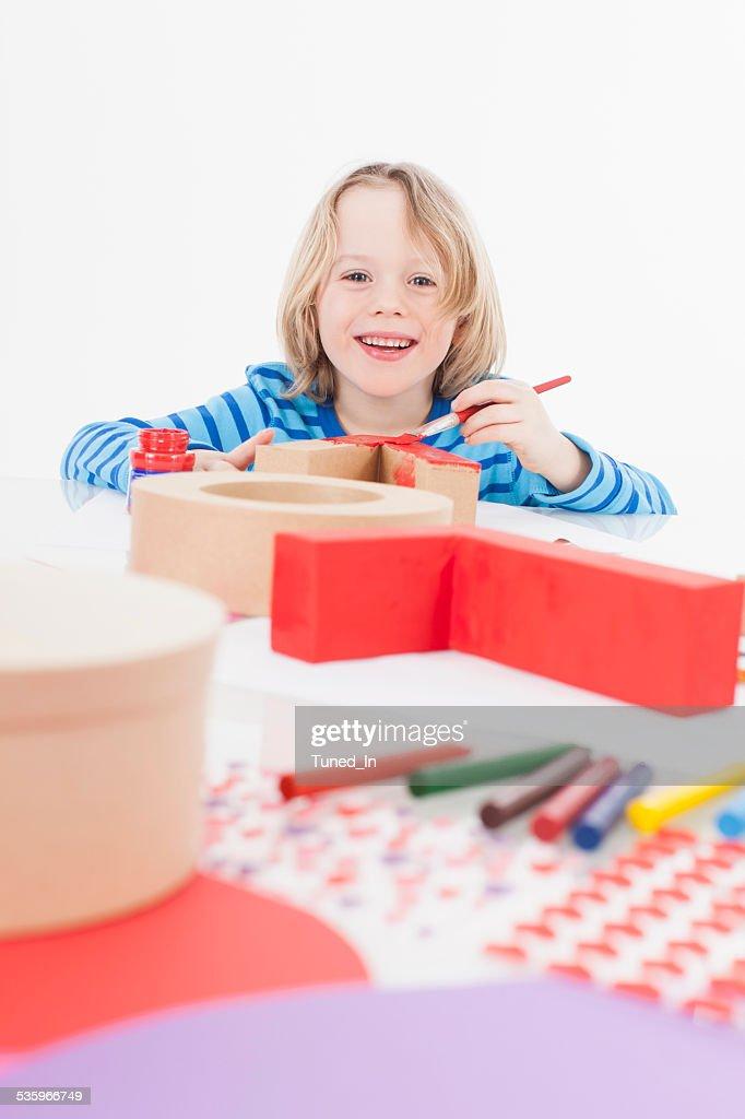 Boy preparing gift, smiling, portrait : Stock Photo