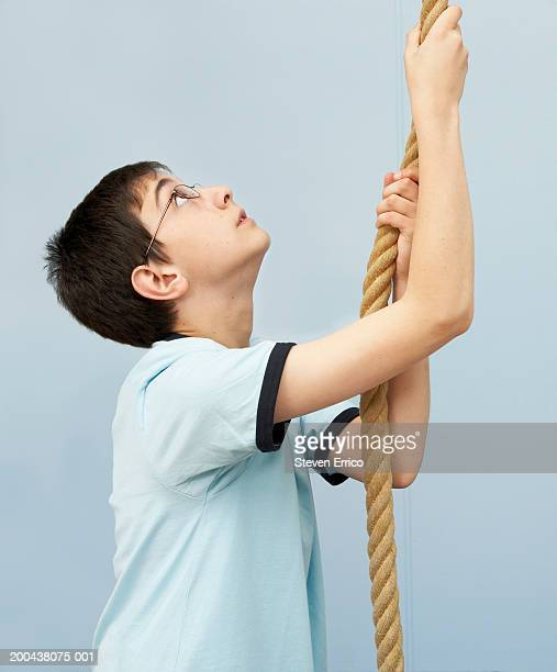 Boy (11-13) preparing to climb rope in school gymnasium, side view
