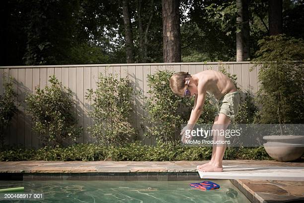 Boy (3-5) preparing to dive into pool, side view