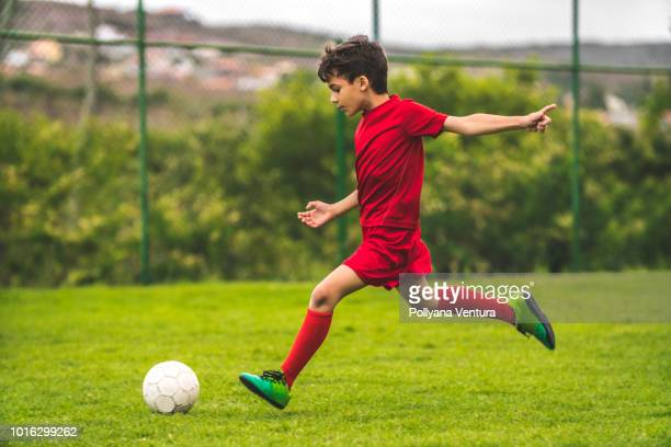 boy preparing to kick the ball - kicking stock pictures, royalty-free photos & images