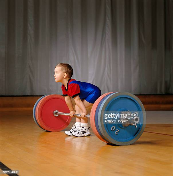 Boy Preparing to Lift Barbell and Weights