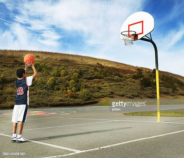 boy (9-1) preparing to shoot basketball, rear view - basketball hoop stock pictures, royalty-free photos & images