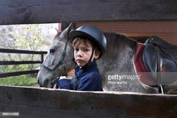 boy prepping horse in a stable