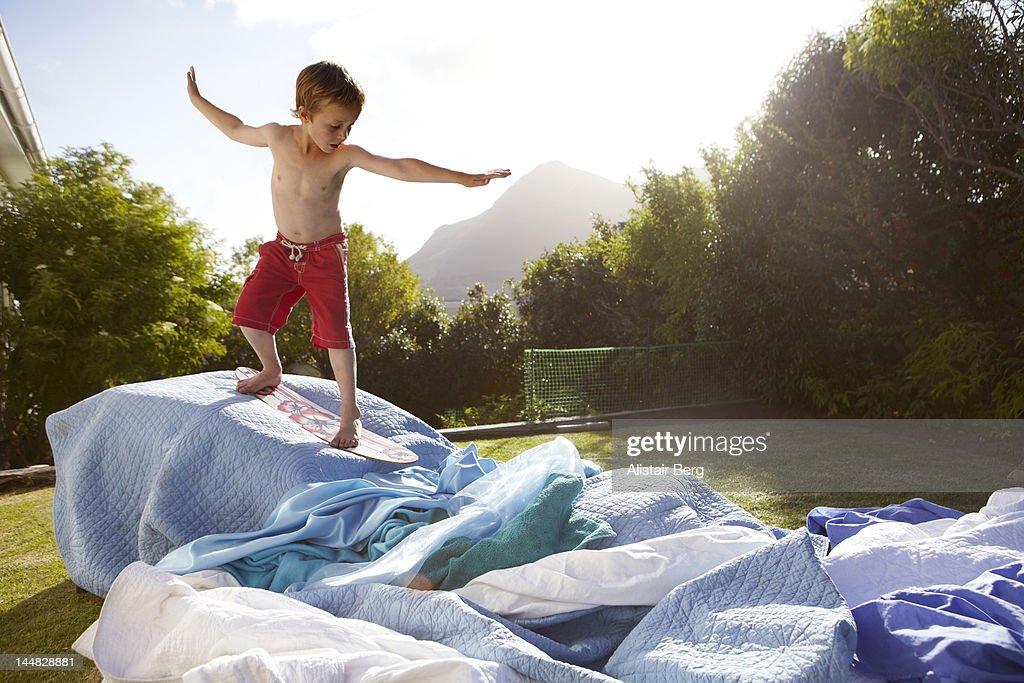 Boy pretending to be a surfer in a suburban garden : Stock-Foto