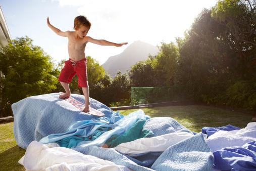 Boy pretending to be a surfer in a suburban garden - gettyimageskorea