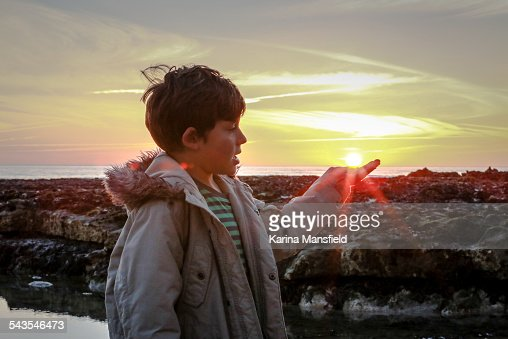 Boy pretending to be holding the sun