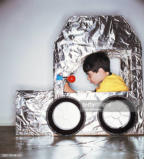 Boy (8-10) pretending to drive cardboard box car, side view