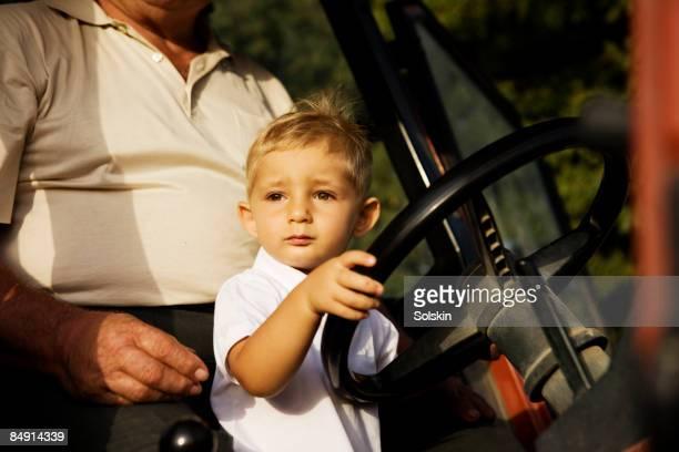 boy pretending to drive tractor