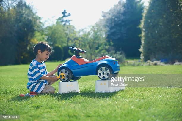 Boy pretending to fix toy car
