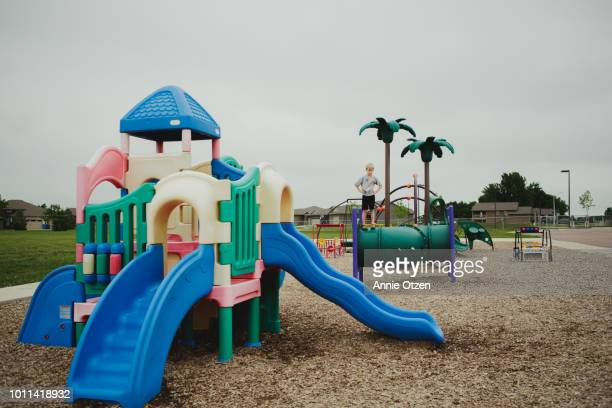 boy proudly standing on public park playground - one boy only stock pictures, royalty-free photos & images