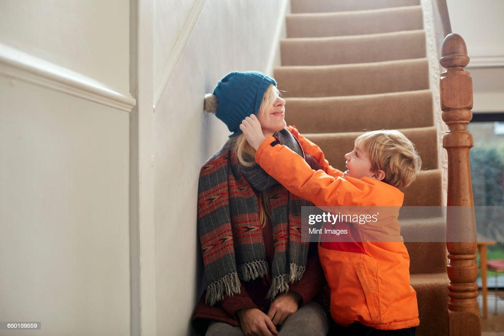 A boy pulling a hat over his mothers eyes. : Stock Photo