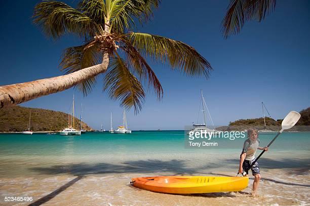 Boy pulling canoe onto shore