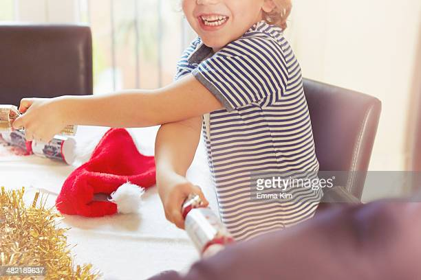 Boy pulling Christmas crackers