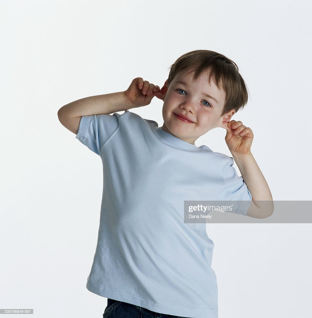 Boy (4-6) pulling ears, smiling, portrait : Stock Photo