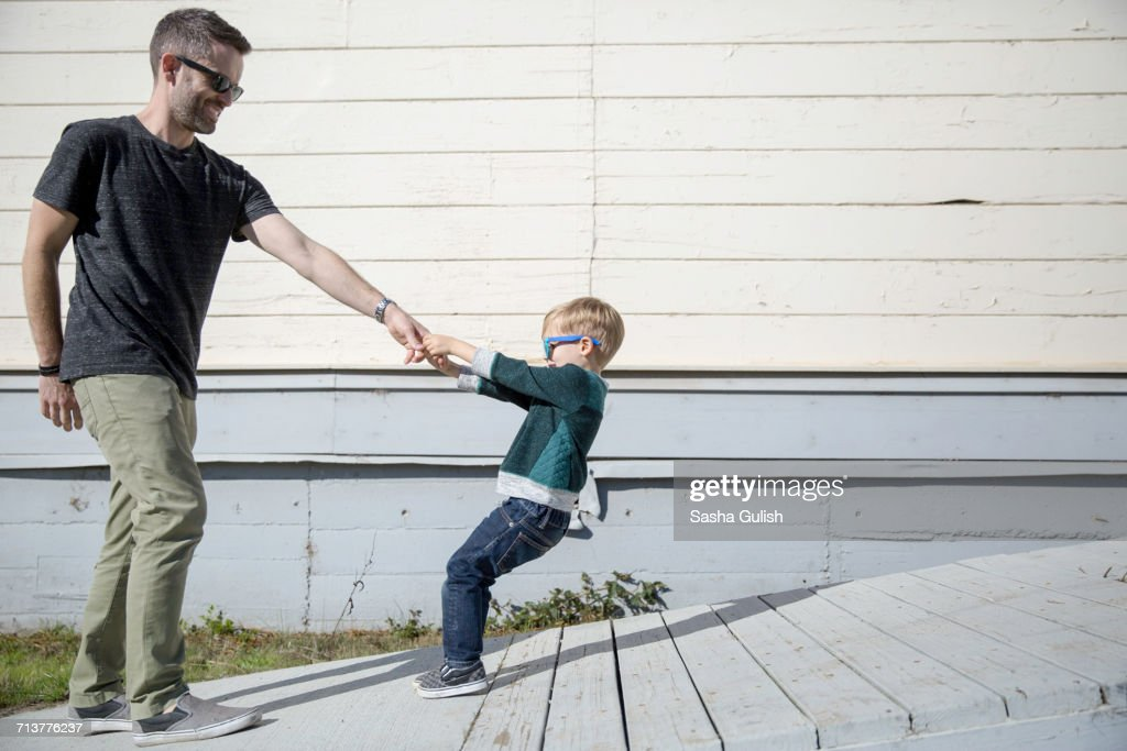 Boy pulling father up wooden ramp : Stock Photo