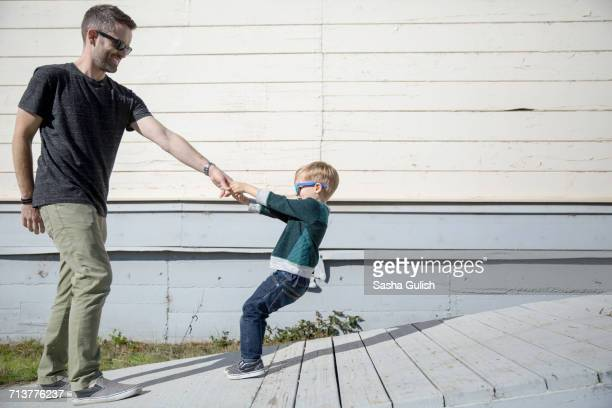 boy pulling father up wooden ramp - american influenced stock photos and pictures