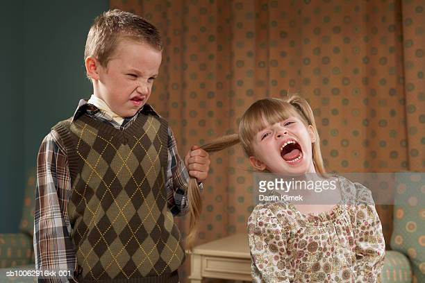 boy (6-7) pulling girl's (4-5) hair in room - bully stock photos and pictures