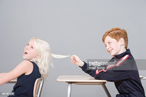 boy pulling girl's hair - girl wrestling stock pictures, royalty-free photos & images