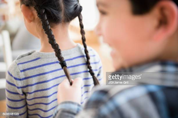 Boy pulling girl's pigtails