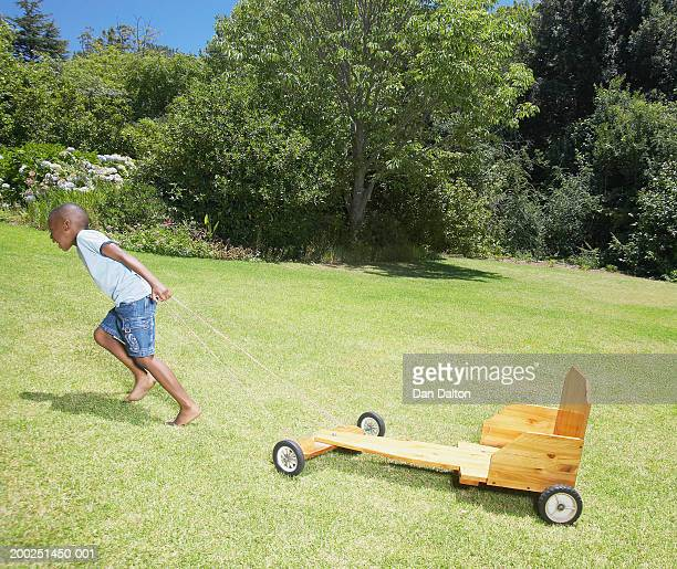 Boy (5-7) pulling go-cart up hill in garden, side view