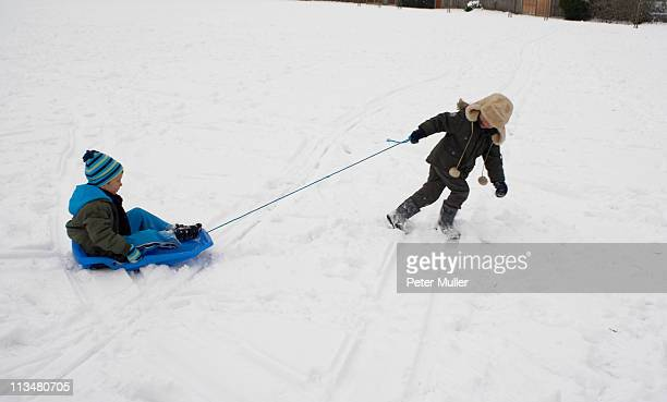 boy pulling his friend on a sledge - tobogganing stock pictures, royalty-free photos & images