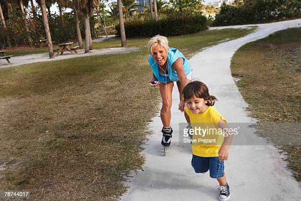 boy pulling inline skater - inline skate stock photos and pictures