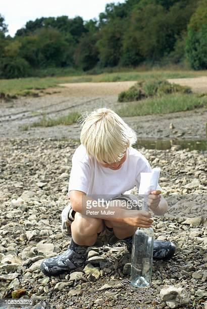 Boy pulling message from bottle