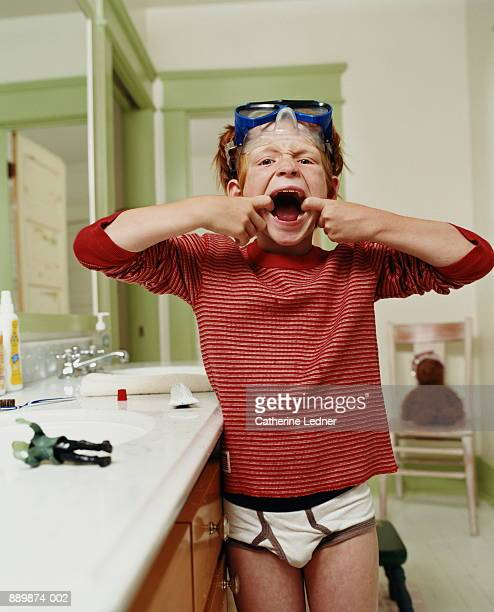 Boy (6-8) pulling mouth after brushing teeth, goggles on head