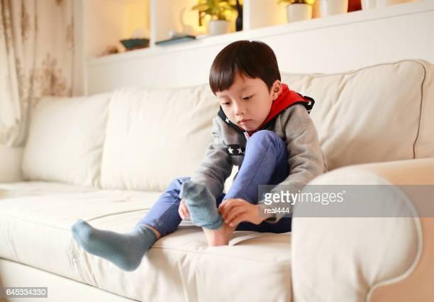 Boy pulling on socks