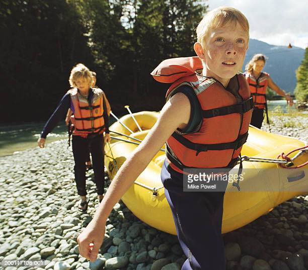 Boy (8-10) pulling  river raft to shore with family