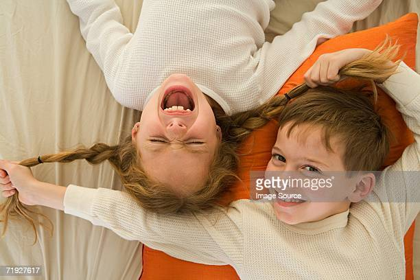 boy pulling sister's pigtails - rough housing stock photos and pictures