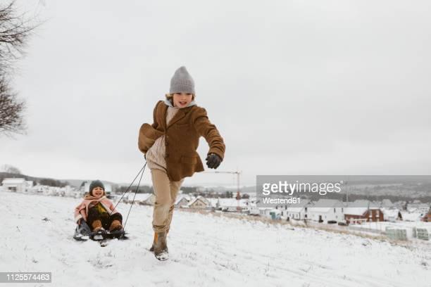 boy pulling sledge with little sister in snow - schlitten stock-fotos und bilder