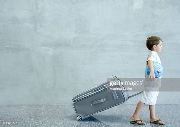 Boy pulling suitcase and carrying globe under arm